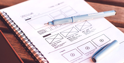 Notepad and pen showing a wireframe sketch of content layout