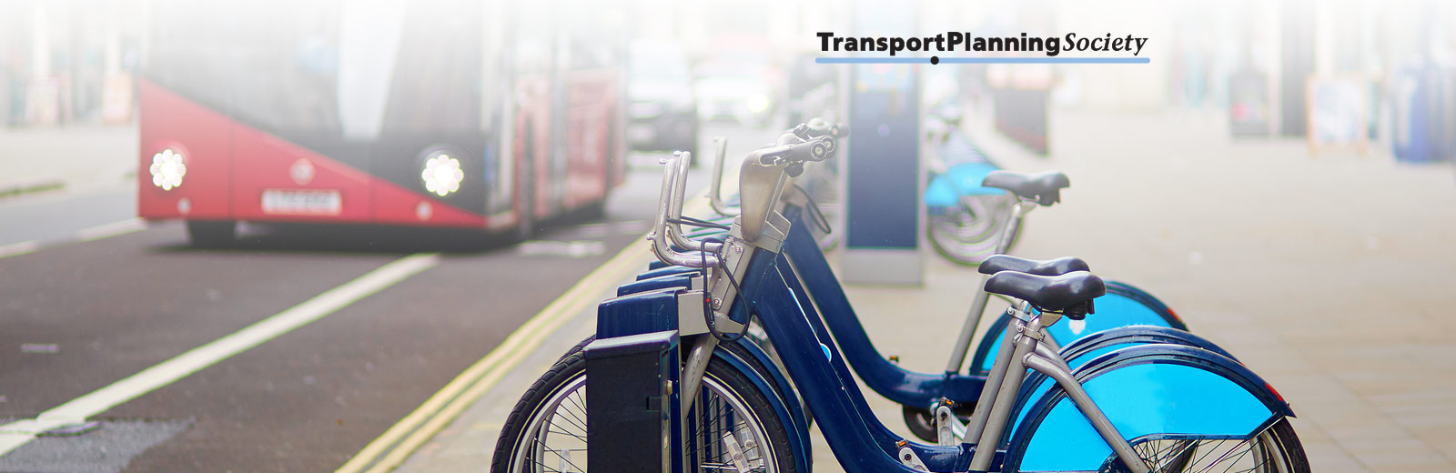 A row of blue bicycles on a London street with a London bus in the background